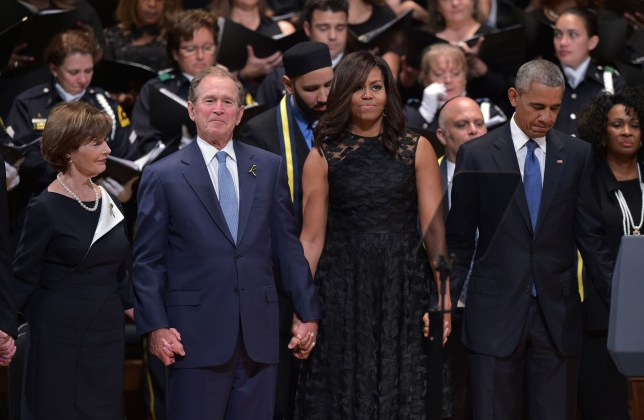 "TOPSHOT - L-R: Former first lady Laura Bush, former US president George W. Bush, US First Lady Michelle Obama and US President Barack Obama join hands during the singing of ""The Battle Hymn of the Republic"" during an interfaith memorial service for the victims of the Dallas police shooting at the Morton H. Meyerson Symphony Center on July 12, 2016 in Dallas, Texas. President Barack Obama attended a somber memorial Tuesday to five police officers slain in a sniper ambush in Dallas, as he seeks to unify a country divided by race and politics. / AFP PHOTO / MANDEL NGANMANDEL NGAN/AFP/Getty Images"