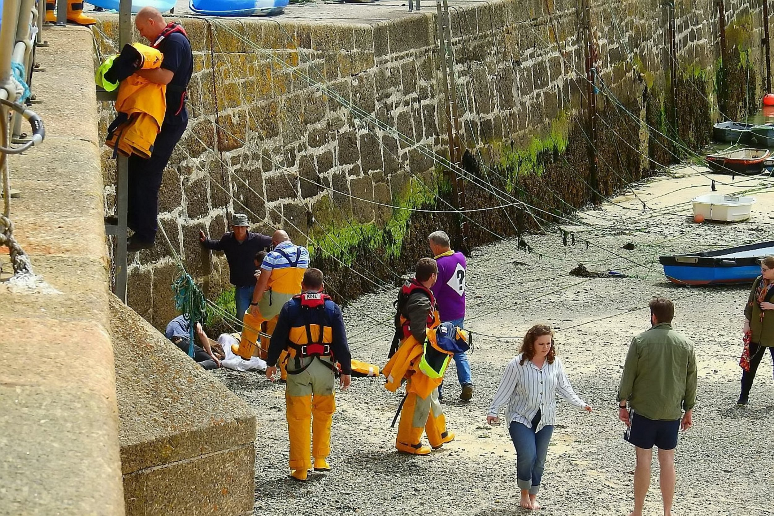 """The scene in St Ives where a girl fell off the sea wall after a seagull flew at her ice cream. See SWNS story SWGULL; A teenager was airlifted to hospital with suspected spinal injuries after plunging 15ft off a harbour wall in St Ives while trying to fend off an attacking seagull. The 18-year-old was eating an ice cream on Smeaton's Pier on Tuesday afternoon when she suddenly fell off the edge onto the beach below. Photographer Chris Oates was at the harbour master's office when he saw the incident and people rush to help the young woman. Mr Oates said: """"There was a young 18-year-old girl sat eating an ice cream near the harbour master's office on Smeaton's Pier. I saw some gulls attacking holiday makers and then they had a go at her and she just fell four to five meters."""