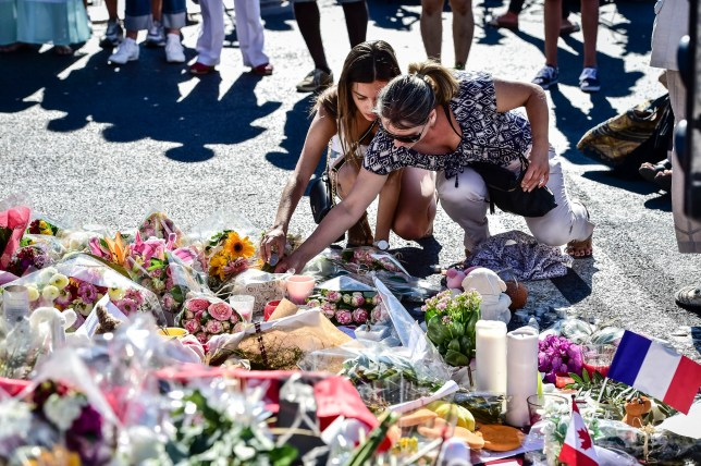 People place candles among tributes on the Promenade des Anglais, Nice, for 84 people dead and scores injured after a terrorist deliberately drove a lorry into Bastille Day revellers, before being fatally wounded in a stand-off with armed police. PRESS ASSOCIATION Photo. Picture date: Saturday July 16, 2016. See PA story POLICE Nice. Photo credit should read: Ben Birchall/PA Wire