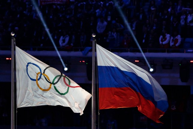 FILE - In this Feb. 23, 2014 file photo the Russian national flag, right, flies after it is hoisted next to the Olympic flag during the closing ceremony of the 2014 Winter Olympics in Sochi, Russia. On Monday, July 18, 2016 a report on Russian doping by investigator Richard McLaren is to be released in Toronto. (AP Photo/Matthias Schrader, file)