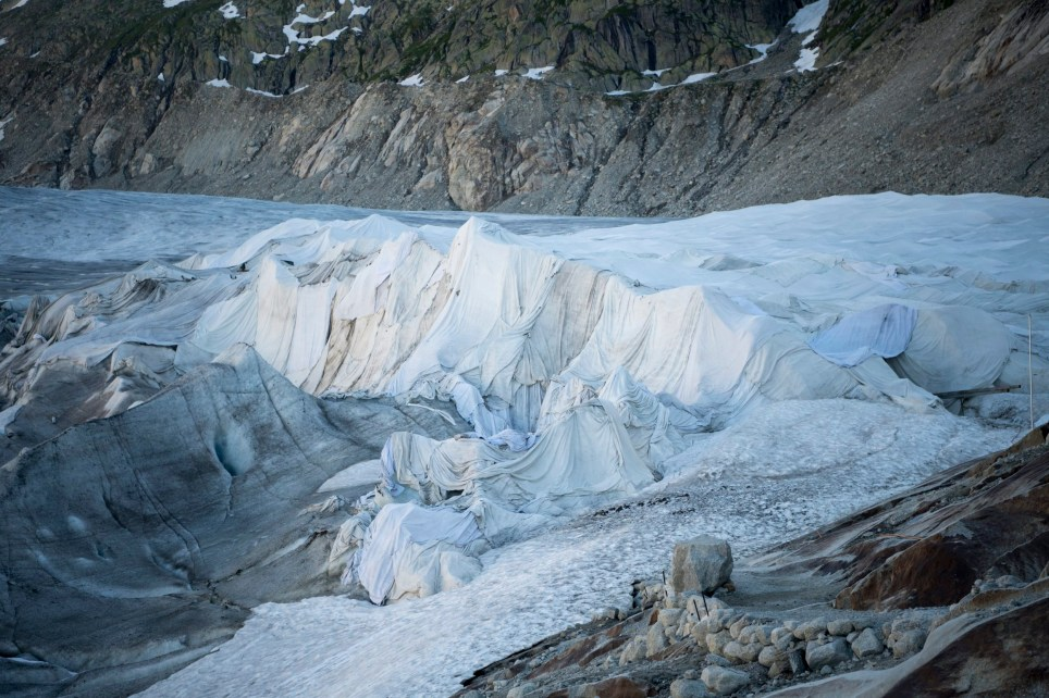 epa05431950 A general view over the Rhone Glacier covered in white blankets above Gletsch near the Furkapass in Switzerland 19 July 2016. The Alps oldest glacier is protected by special white blankets to prevent it from melting. EPA/URS FLUEELER