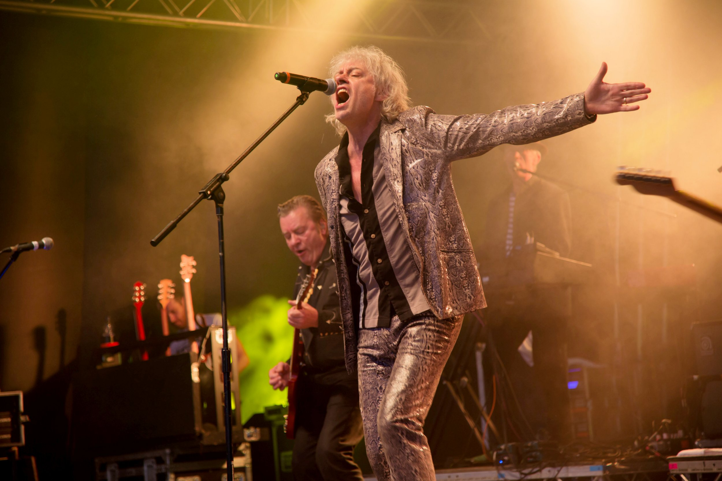 """Bob Geldof and the Boomtown Rats perform at the Brentwood Festival, 2016. See Masons copy MNGELDOF: Hundreds of fans walked out of a festival as millionaire singer Bob Geldof launched a foul-mouthed rant at them - for wearing Primark clothes. The Boomtown Rats big mouth also stopped after one song and insulted the family event for being so tame. The band had been booked to headline the two-day Brentwood Festival in Essex last weekend. But Geldof started swearing at soon as they came on stage, shouting: """"We don't do Abba. We don't do Robbie f*****g Williams."""