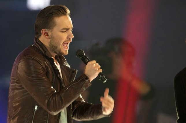 FILE - This is a Friday, Dec. 12, 2014 file photo of One Direction singer Liam Payne as he performs with the group, on stage during the ceremony of the '40 Principales Awards 2014' at Palacio de los Deportes in Madrid, Spain. One Direction fans are seeing the writing on the wall as singer Liam Payne announced Friday July 22, 2016 that he has signed a record deal with Capitol Records UK after the boy band said last year they were taking a break. (AP Photo / Abraham Caro Marin, File)
