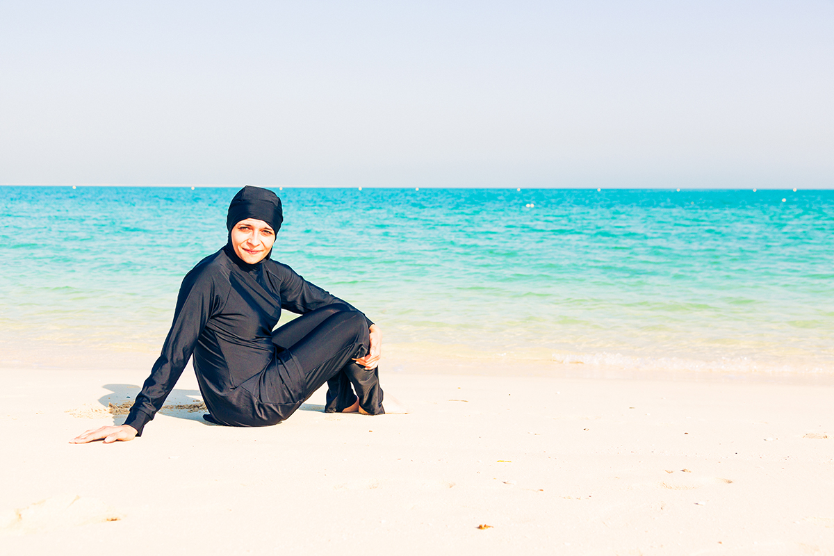 young woman wearing burkini sitting by the beach in dubai Credit: Getty Images