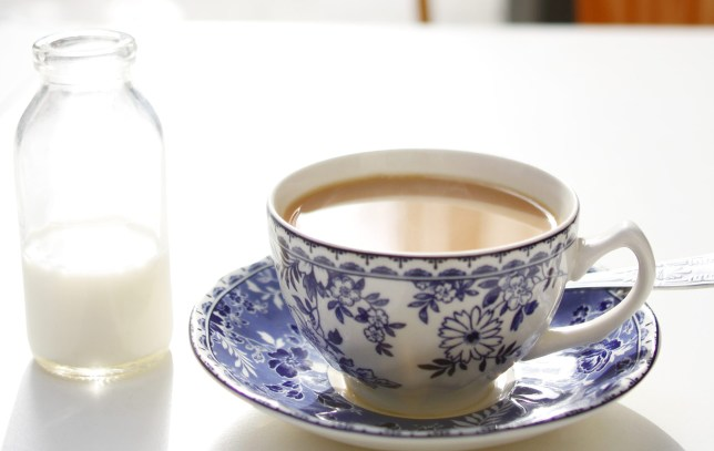 A hot cup of British tea is sat upon a white table with a small bottle of milk.