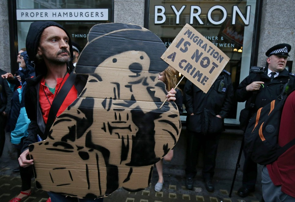 """Protestors hold a demonstration outside a Byron burger restaurant in Holborn, central London on August 1, 2016. The arrest of dozens of staff from the upmarket British burger chain Byron by immigration officials reportedly tipped off by the management prompted an outcry and calls for a boycott. The interior ministry confirmed that 35 people from Albania, Brazil, Egypt and Nepal had been arrested in several Byron restaurants in London on July 4 during """"intelligence-led visits"""". / AFP PHOTO / Justin TALLISJUSTIN TALLIS/AFP/Getty Images"""