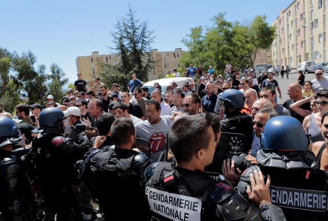 """Hundreds walk into the cite des Monts surrounded by policemen in Lupino on August 14, 2016 in Bastia on the French Mediterranean island of Corsica. Approximately 500 people gathered on Sunday morning at the housing estate """"des Monts"""" in Bastia's Lupino neighbourhood, the day after a violent fight occurred in a creek by the sea in Sisco (Haute-Corse) leaving four wounded, according to a journalist of AFP. A minor girl who witnessed the confrontation, talking through a megaphone, explained the fight happened after a group of youngsters of Maghreb origin insulted tourists who were photographing women bathing in burkini. / AFP PHOTO / PASCAL POCHARD-CASABIANCAPASCAL POCHARD-CASABIANCA/AFP/Getty Images"""