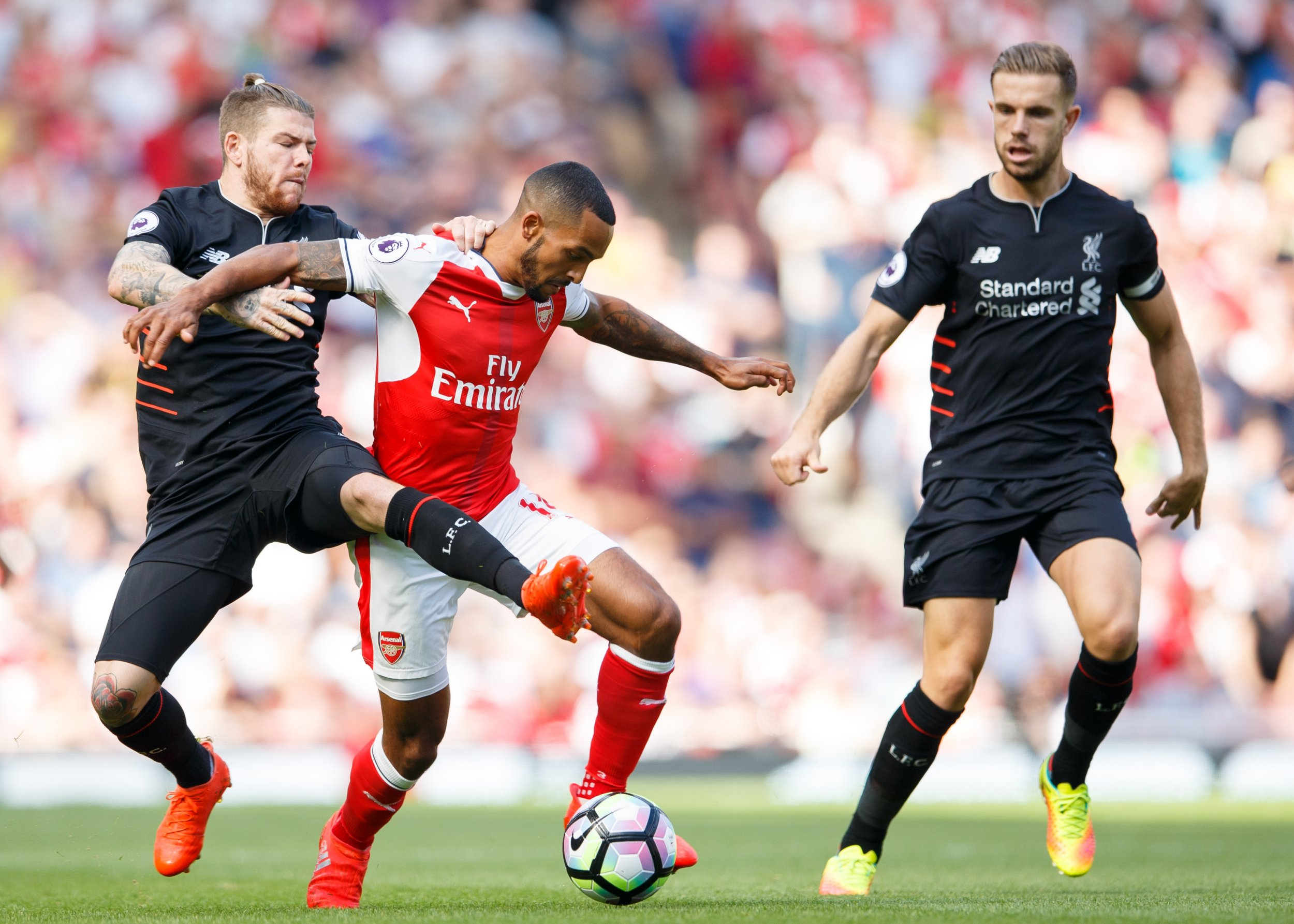 Theo Walcott of Arsenal takes on Alberto Moreno and Jordan Henderson of Liverpool during the Premier League match between Arsenal and Liverpool played at The Emirates Stadium, London on 14th August 2016