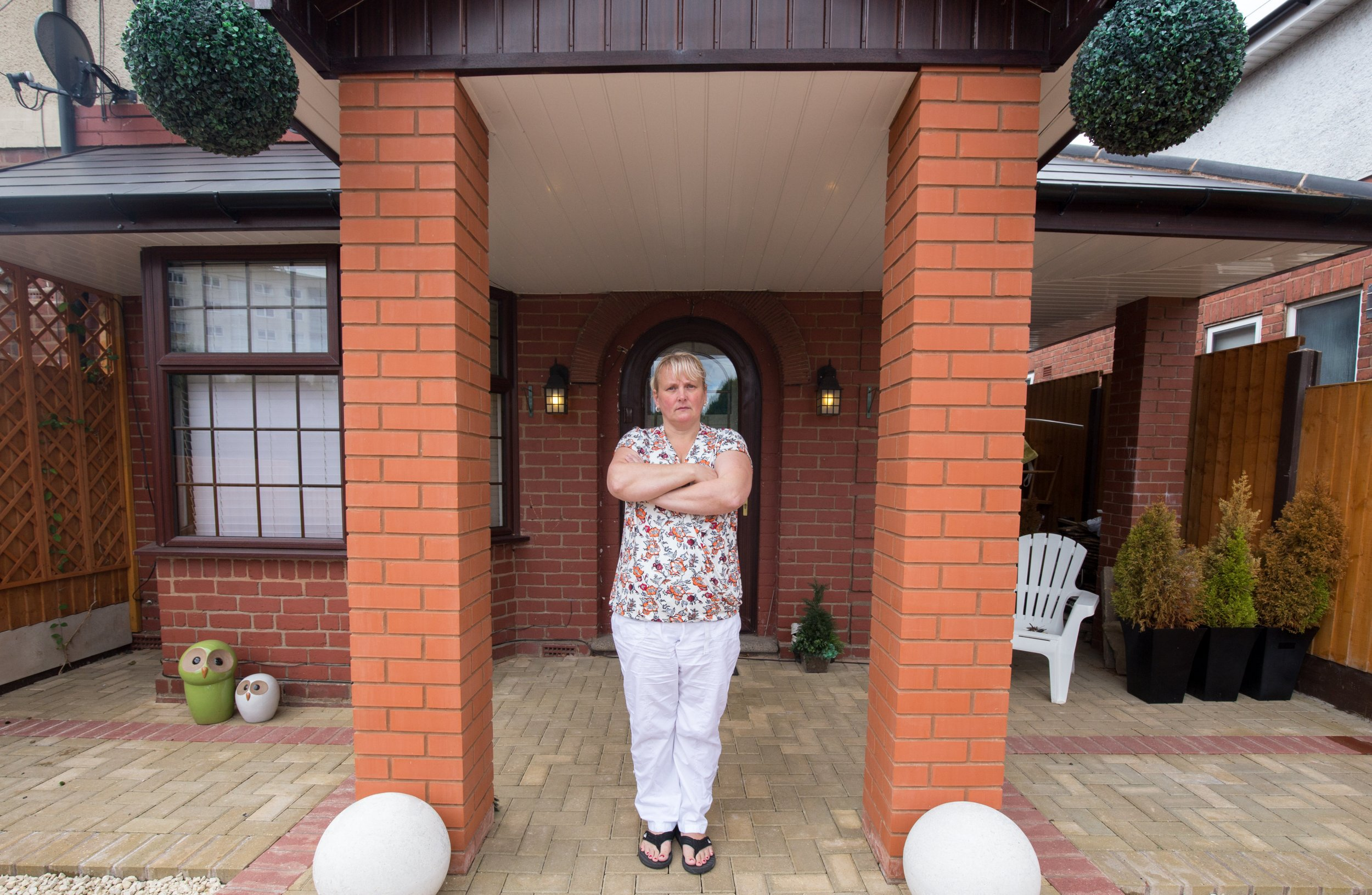 """Nicola stands outside her home on West Bulevard, Quinton, Birmingham. August 21 2016. See News Team story NTIHOUSE: A family who invested their life savings in an £11,000 extension have been ordered to tear down the build, despite getting the plans approved three years ago. Nicola Graham-O'Connor, 49, was shocked when she received a letter three weeks after completing the work giving her just 28 days to get rid of it. She claimed Birmingham Council told her she didn't need permission before adding the pillars, canopy and railings onto her semi-detached property three years ago. But council workers have now said it is """"out of character"""", """"out of scale"""" and """"dominating"""" and said retrospective planning permission is """"unlikely to be forthcoming""""."""