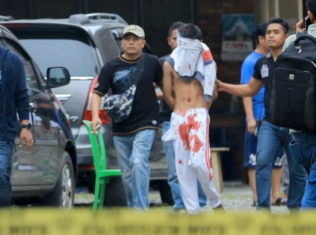 epa05512631 An Indonesian plainclothes policemen detains a terrorist suspect (C) after an  attempted suicide bombing at St. Yoseph Catholic Church  in Medan, Indonesia, 28 August 2016. An unidentified man attempted a suicide bombing with a small bomb and only injured himself, with no other casualties reported.  EPA/DEDI SINUHAJI