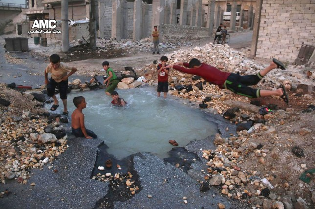 This Wednesday, Aug. 31, 2016 photo, provided by the Syrian anti-government activist group Aleppo Media Center (AMC), shows Syrian boys dive into a hole filled with water that was caused by a missile attack in the rebel-held neighborhood of Sheikh Saeed in Aleppo province, Syria. (Aleppo Media Center via AP)