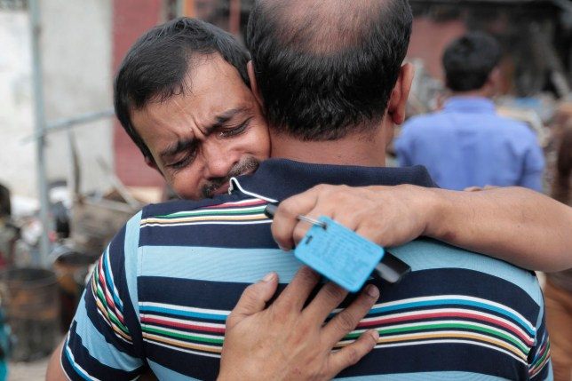 A factory employee is comforted as he cries near a packaging factory which was burnt down by a fire in Tongi industrial area outside Dhaka, Bangladesh, Sunday, Sept. 11, 2016. A boiler exploded and triggered a fire Saturday at Tampaco Foils Ltd. factory. (AP Photo/A. M. Ahad)