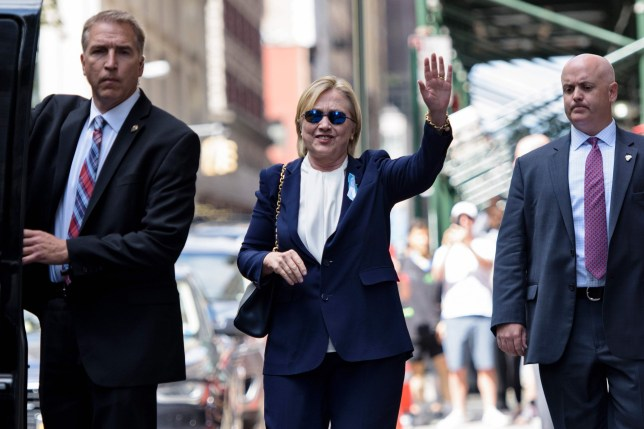"""US Democratic presidential nominee Hillary Clinton waves to the press as she leaves her daughter's apartment building after resting on September 11, 2016 in New York. Clinton departed from a remembrance ceremony on the 15th anniversary of the 9/11 attacks after feeling """"overheated,"""" but was later doing """"much better,"""" her campaign said. / AFP PHOTO / Brendan SmialowskiBRENDAN SMIALOWSKI/AFP/Getty Images"""