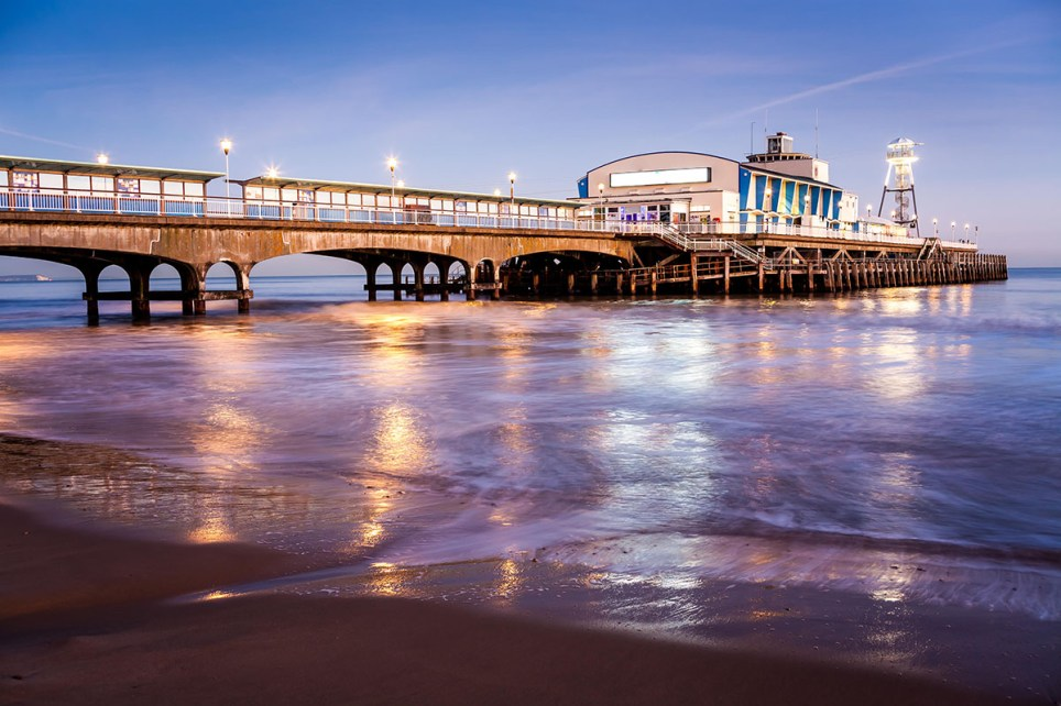 pic - alamy EJ62GY The lights of Bournemouth Pier at night reflected in the wet sand on the beach. Dorset England UK Europe.