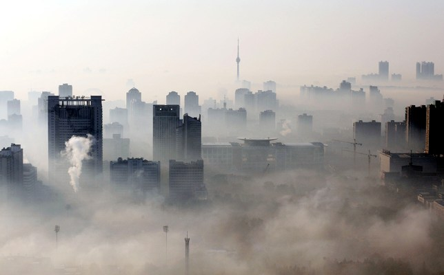 An aerial view of buildings standing out amid haze engulfing Wuhan, central China's Hubei province on December 3, 2009. China will need to invest up to 30 billion dollars a year to meet its goal of curbing greenhouse gas emissions, the state press said, citing an academic study, as Beijing set its targets before world leaders gather in Copenhagen this month for talks on negotiating a new global warming pact to replace the Kyoto Protocol that expires in 2012. CHINA OUT AFP PHOTO (Photo credit should read STR/AFP/Getty Images)