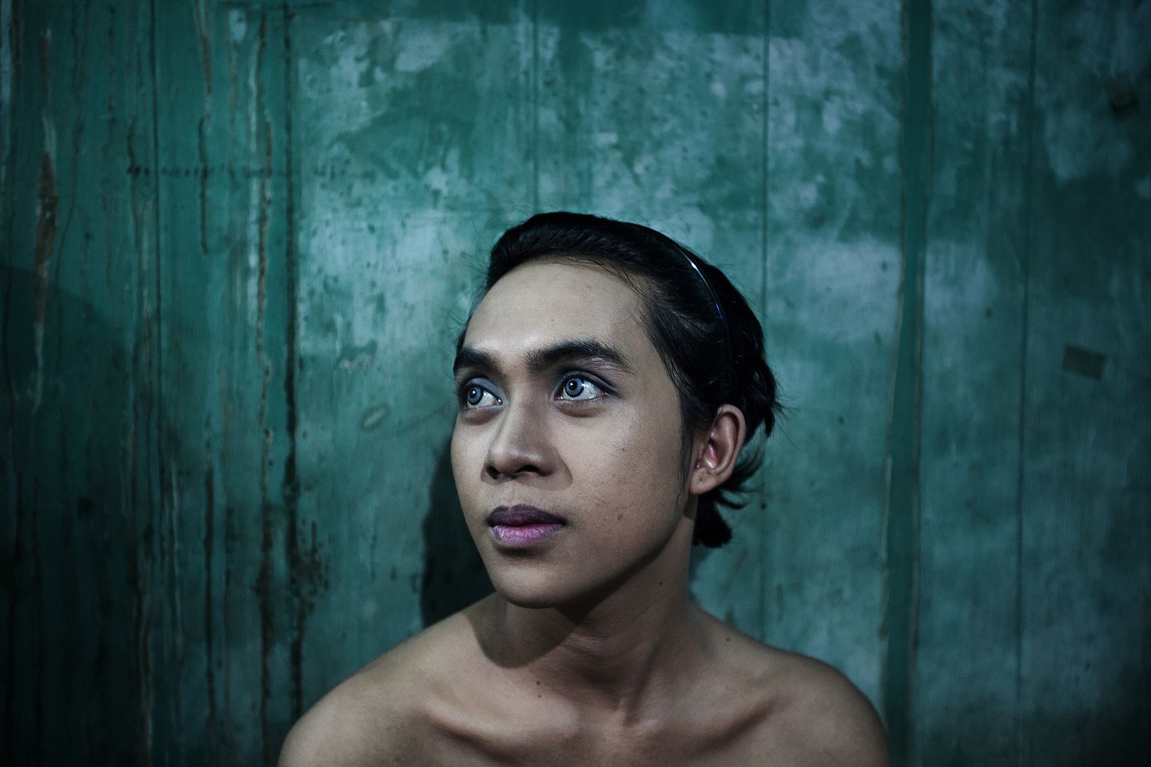 A young transgender puts make up on in his bedroom at Mami Joyce's house.