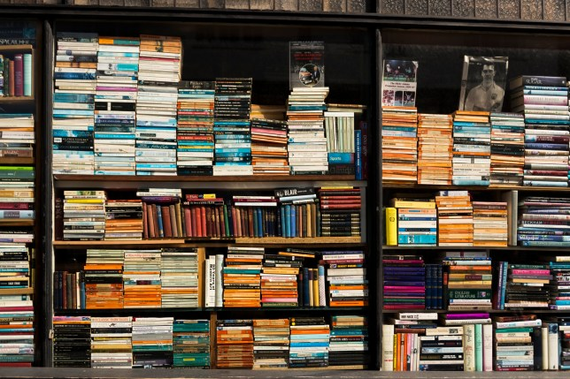 Colourful book edges arranged against the shop window of a bookshop, London, UK