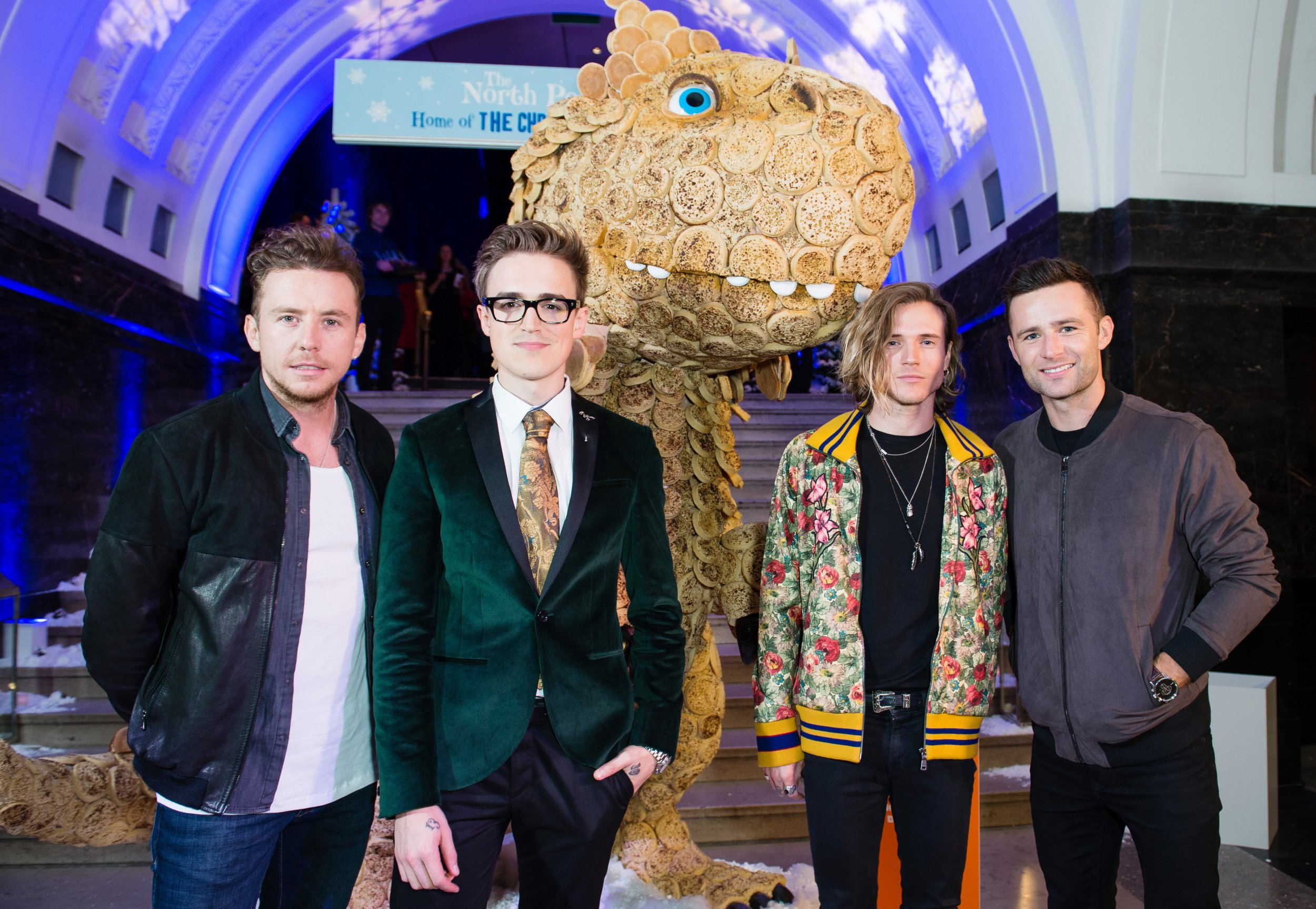 LONDON, ENGLAND - OCTOBER 05: (L-R) Danny Jones, Tom Fletcher, Dougie Poynter and Harry Judd from McFly meet the 'Giant Crumpet Christmasaurus'. Warburtons created a 'Giant Crumpet Christmasaurus' crafted from Warburtons Giant Crumpets, marking the launch of Tom FletcherÕs new book, The Christmasaurus at Natural History Museum on October 5, 2016 in London, England. (Photo by Jeff Spicer/Getty Images for Warburtons)