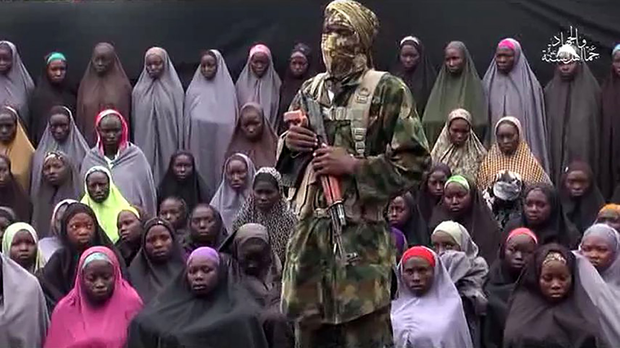 "(FILES) This video grab image created on August 14, 2016 taken from a video released on youtube purportedly by Islamist group Boko Haram showing what is claimed to be one of the groups fighters at an undisclosed location standing in front of girls allegedly kidnapped from Chibok in April 2014. A Nigerian government official announced on October 13, 2016 that Boko Haram had released 21 of the 276 schoolgirls kidnapped by the group from Chibok in April 2014 . / AFP PHOTO / HO / RESTRICTED TO EDITORIAL USE - MANDATORY CREDIT ""AFP PHOTO / BOKO HARAM"" - NO MARKETING NO ADVERTISING CAMPAIGNS - DISTRIBUTED AS A SERVICE TO CLIENTS HO/AFP/Getty Images"