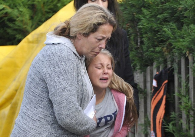Tearful scenes as Sara Broadhead and daughter Mia read the hundreds of tributes that had been left at the scene of the fire. A murder investigation has been launched after an eight-year-old girl and her father were killed as he tried to save her from a house fire. See ROSS PARRY story RPYFIRE. Andrew Broadhead, 42, and daughter Kiera died in the blaze at the family home in Wakefield, West Yorkshire, on Wednesday morning, just hours after returning from holiday. Mother Sara, 35, and 13-year-old daughter Mia suffered only minor injuries after climbing out through a window. Mr Broadhead, a railway engineer, initially escaped the blaze but went back into the house to try and rescue his youngest daughter.