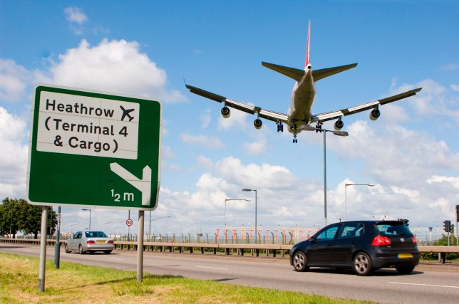 Cars on the A4 passing a road sign for Heathrow airport as a plane comes into land directly overhead.