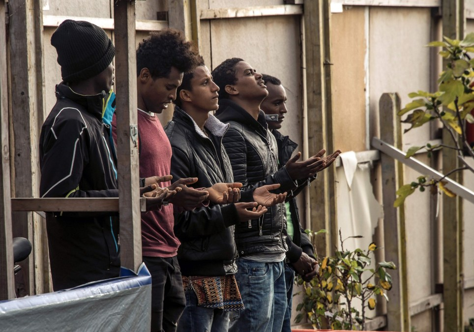 """Ethiopian Coptic migrants pray as they arrive for a mass at the makeshift Orthodox church in the Jungle"""" migrant camp, on October 30, 2016. French President Francois Hollande on October 29, 2016 urged Britain to take in 1,500 unaccompanied minors from the """"Jungle"""" as officials stepped up efforts to finish demolishing the almost-deserted Calais migrant camp. Hailing the evacuation of the sprawling encampment, Hollande vowed that France would not accept the emergence of any more makeshift camps, which have become a glaring symbol of Europe's worst migration crisis since World War II. / AFP PHOTO / PHILIPPE HUGUENPHILIPPE HUGUEN/AFP/Getty Images"""