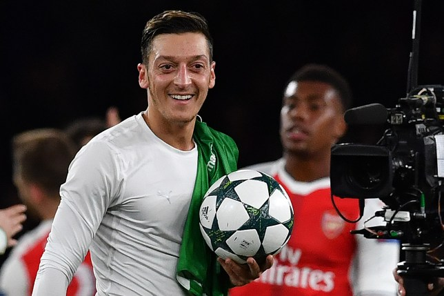 Arsenal's German midfielder Mesut Ozil (L) carries the match ball following the UEFA Champions League Group A football match between Arsenal and Ludogorets Razgrad at The Emirates Stadium in London on October 19, 2016. / AFP / BEN STANSALL        (Photo credit should read BEN STANSALL/AFP/Getty Images)