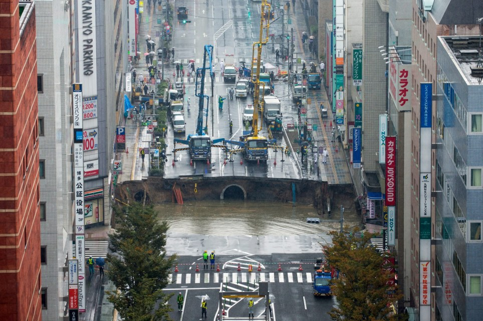 epa05621785 A large sinkhole cuts off an avenue in central Fukuoka, southwestern Japan, 08 November 2016. According to local media reports, the sinkhole has caused blackouts and disrupted traffic. Authorities have evacuated surrounding buildings in case of further damage. There were no immediate reports of damage or injuries. EPA/HIROSHI YAMAMURA