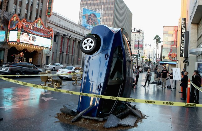HOLLYWOOD, CA - NOVEMBER 15: A car 'crashed' into the ground on November 15, 2016 at the Walk of Fame in Hollywood, California, ahead of the launch of Jeremy Clarkson, Richard Hammond and James May's new show, 'The Grand Tour', on Amazon Prime Video, on Friday. (Photo by Randy Shropshire/Getty Images for Amazon Prime Video)