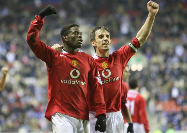 Wigan, UNITED KINGDOM: Manchester United's Louis Saha (L) and captain Gary Neville celebrate after Wigan Athletic's Pascal Chimbonda scored an own goal during their English Premiership soccer match at The JJB Stadium, in Wigan, 06 March 2006. AFP PHOTO/PAUL ELLIS Mobile and website use of domestic English football pictures subject to subscription of a license with Football Association Premier League (FAPL) tel : +44 207 298 1656. For newspapers where the football content of the printed and electronic versions are identical, no licence is necessary. (Photo credit should read PAUL ELLIS/AFP/Getty Images)