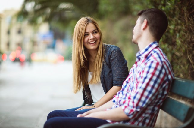 A girl and a guy having a chat on a bench