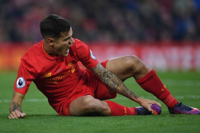 Liverpool's Brazilian midfielder Philippe Coutinho holds his foot as he lies on the pitch injured during the English Premier League football match between Liverpool and Sunderland at Anfield in Liverpool, north west England on November 26, 2016. / AFP / Paul ELLIS / RESTRICTED TO EDITORIAL USE. No use with unauthorized audio, video, data, fixture lists, club/league logos or 'live' services. Online in-match use limited to 75 images, no video emulation. No use in betting, games or single club/league/player publications. / (Photo credit should read PAUL ELLIS/AFP/Getty Images)