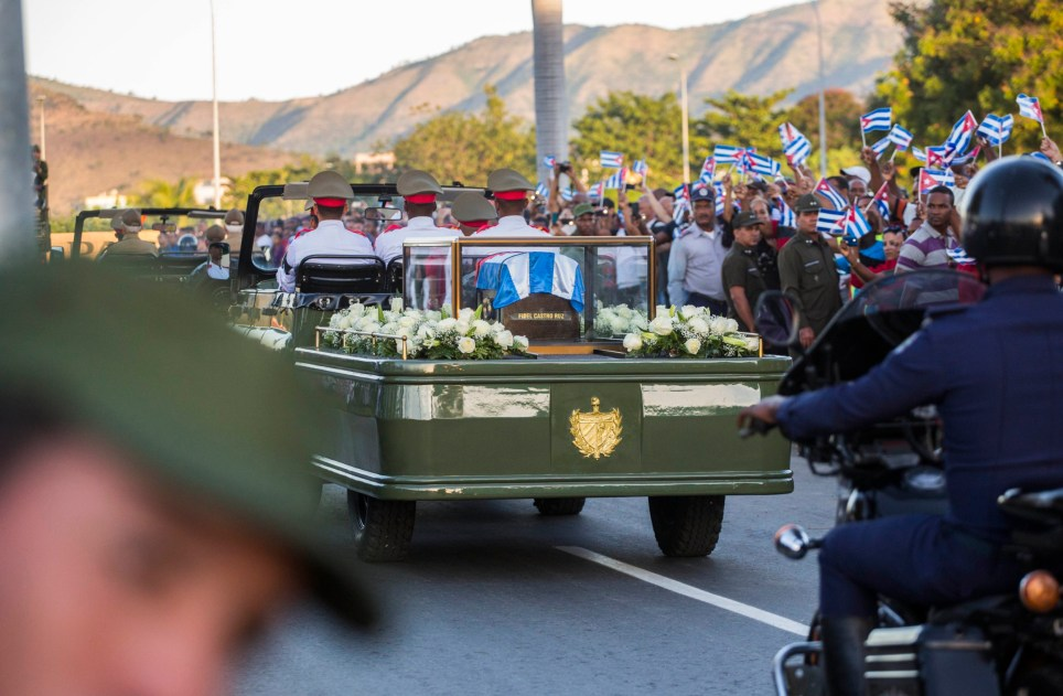 The motorcade carrying the ashes of the late Cuban leader Fidel Castro makes i's final journey towards the Santa Ifigenia cemetery in Santiago, Cuba Sunday, Dec. 4, 2016. Thousands of people lined the short route from the Plaza Antonio Maceo or Plaza of the Revolution to the cemetery where the ashes will be buried in a private ceremony near the grave of Cuba's independence hero Jose Marti. (AP Photo/Desmond Boylan)