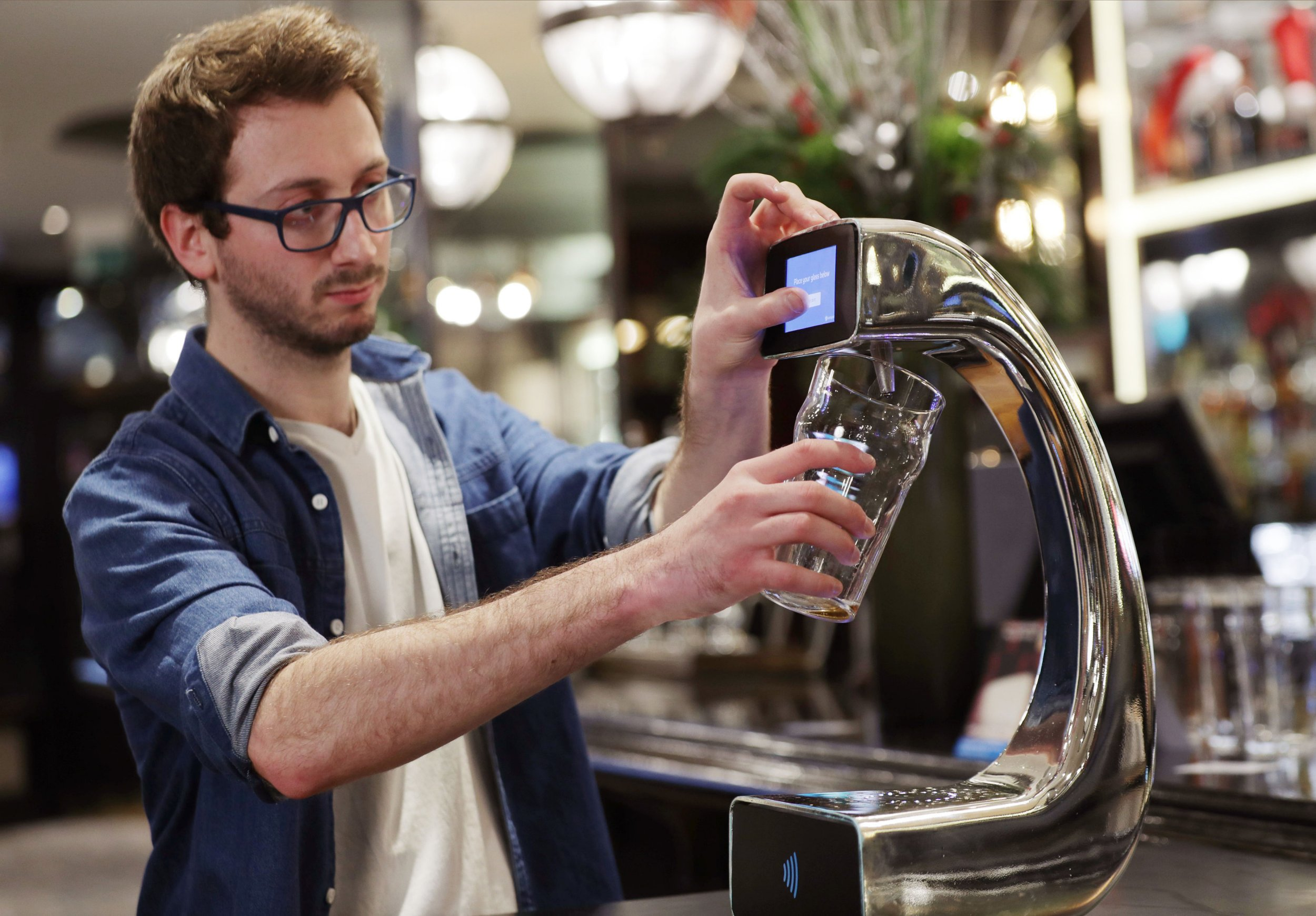 Embargoed to 0001 Friday December 16 James Miller, who helped to develop the worldís first contactless, self-serving beer pump with Barclaycard to help cut bar queues on nights out, takes part in a demonstration at Henryís Cafe and Bar in Piccadilly, London. PRESS ASSOCIATION Photo. Picture date: Monday December 12, 2016. Called Pay @ Pump, the prototype has been designed to help speed up drinks service during busy times of year, including Christmas, by enabling customers to select their drink of choice, pay by tapping their contactless card or device against the base of the pump and then placing a glass on it to begin pouring their drink automatically. See PA story TECHNOLOGY Pump. Photo credit should read: Yui Mok/PA Wire