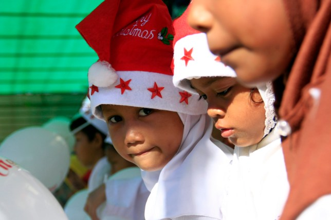 MANADO, NORTH SULAWESI, INDONESIA - 2015/12/12: Muslim children in the city of Manado join the Christmas Santa Parade wearing Santa hats and mingle with Christians. (Photo by Ronny Adolof Buol/Pacific Press/LightRocket via Getty Images)