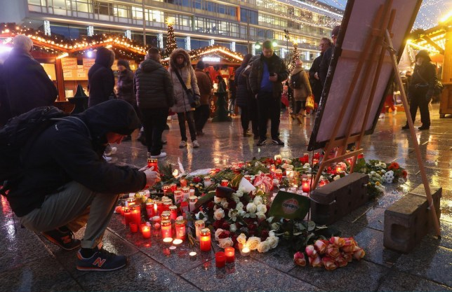 BERLIN, GERMANY - DECEMBER 22: A visitor lays a candle at a makeshift memorial inside the reopened Breitscheidplatz Christmas market only a short distance from where three days ago a truck plowed into the market, killed 12 people and injured dozens in a terrorist attack on December 22, 2016 in Berlin, Germany. The Breidscheidplatz Christmas market is reopening today, though its small amusement rides and bright lights displays will remain shut off in a sign of continuing mourning for the attack victims. Meanwhile police have launched a European-wide manhunt for Anis Amri, a 24-year-old Tunisian man they suspect of having driven the truck. (Photo by Sean Gallup/Getty Images)