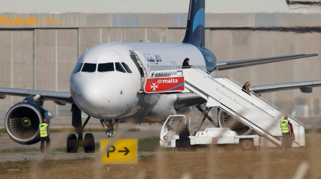 People disembark from a hijacked Libyan Afriqiyah Airways Airbus A320 on the runway at Malta Airport, December 23, 2016. REUTERS/Darrin Zamit-Lupi   MALTA OUT