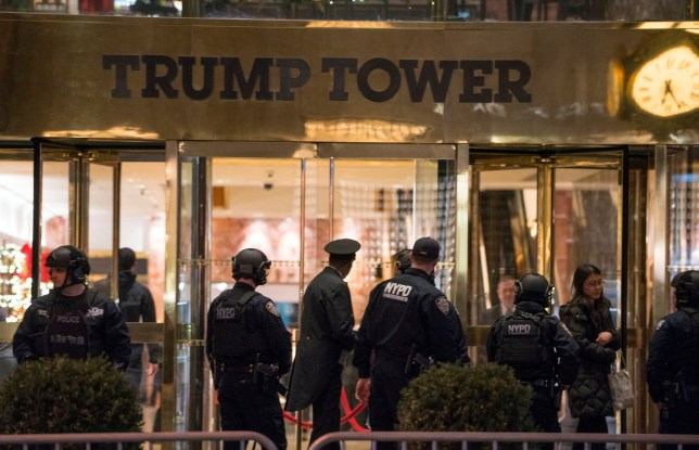 New York police officers and others stand outside the Trump Tower lobby in New York, Tuesday, Dec 27, 2016. Police hastily cleared the lobby of Trump Tower on Tuesday to investigate an unattended backpack, only to find that the bag contained children's toys (AP Photo/Craig Ruttle)
