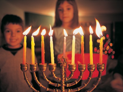 What is a Hanukkah candle called and when do you light them?
