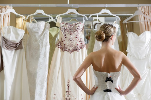 Bride looking at rack of dresses