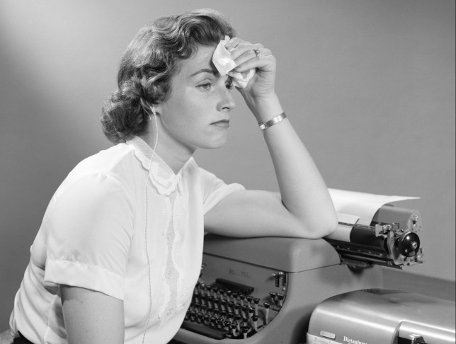 1950s AILING WOMAN SECRETARY SITTING AT DESK WITH TYPEWRITER AND DICTATION MACHINE HOLDING HANDKERCHIEF TO FOREHEAD (Photo by H. Armstrong Roberts/ClassicStock/Getty Images)