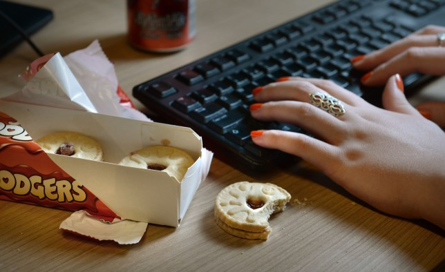 "File photo dated 29/08/14 of an office worker eating a biscuit at her desk, as workers should cut workplace ""cake culture"" in a bid to get healthy in 2017, leading dentists have said. PRESS ASSOCIATION Photo. Issue date: Tuesday January 3, 2017. See PA story HEALTH Sugar Cake. Photo credit should read: Anthony Devlin/PA Wire"