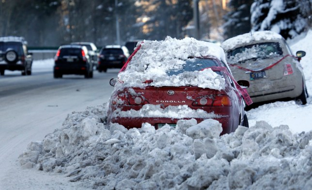 Early morning traffic slides by stranded cars in Portland, Ore., Thursday, Jan. 12, 2017. Schools were closed and more than 5,000 Portland General Electric customers remained without power Thursday as the Portland area recovers from a snowstorm. (AP Photo/Don Ryan)