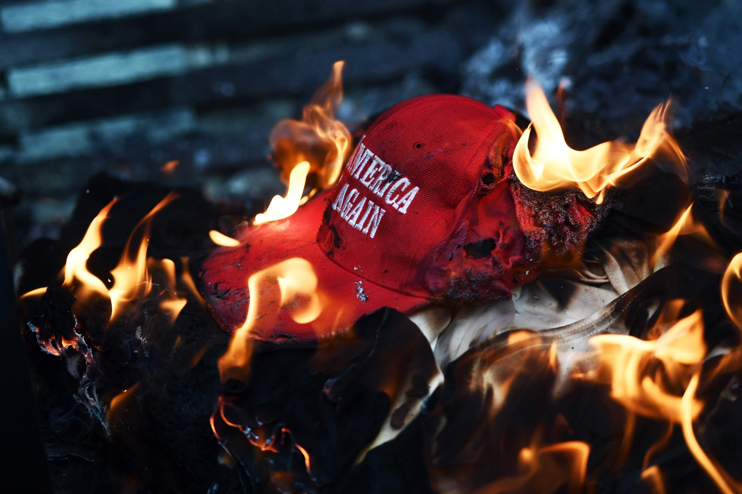 """Anti-Trump demonstrator set a """"Make America Great Again"""" hat on fire in Washington, DC, on January 20, 2107. Masked, black-clad protesters carrying anarchist flags smashed windows and scuffled with riot police Friday in downtown Washington, blocks away from the route of the parade in honor of newly sworn-in President Donald Trump. / AFP PHOTO / Jewel SAMADJEWEL SAMAD/AFP/Getty Images"""