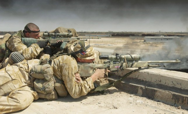 BASRA, IRAQ - APRIL 3:  In this hand out image by the British Defence Ministry, (L-R) Lance Sergeant Chris Briggs and Guardsman Warren Bradford serve as a snipers with Support Company attached to Number 1 Company 1st Battalion The Irish Guards April 3, 2003 in Basra, Iraq. In a dawn raid on a university factory complex within sight of their patrol base at Bridge Four on the outskirts of Basra, the Irish Guards attacked and cleared the base after coming under fire from small arms mortars and SAM Missile systems, which were fired from Iraqi positions at a British Lynx Helicopter supporting the Irish Guards. Briggs and Bradford are one of four sniper pairs set up within the buildings to provide covering fire for the Royal Engineers attempting to put out one of the numerous oil well fires.  (Photo by Giles Penfound/MOD/Getty Images)