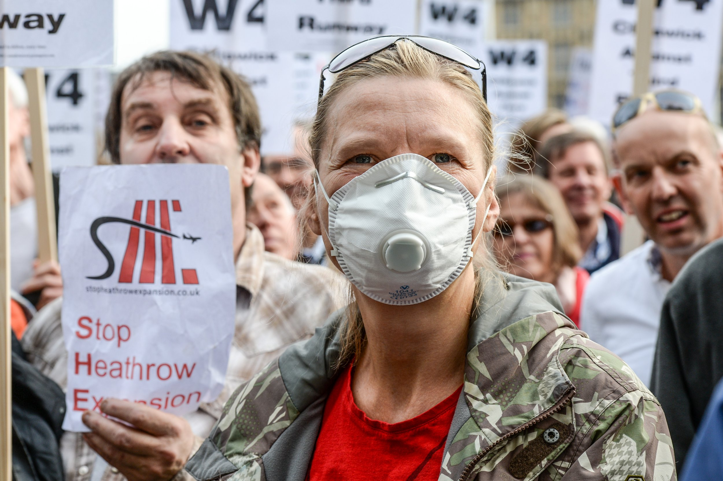 LONDON, ENGLAND - OCTOBER 10: Protesters hold signs during a rally against a third runway at Heathrow airport, in Parliament Square on October 10, 2015 in London, England. Before today's rally against a third runway at Heathrow, Parliamentary hearings were announced yesterday to investigate whether the increase in flight traffic will break toxic air limits. (Photo by Chris Ratcliffe/Getty Images)