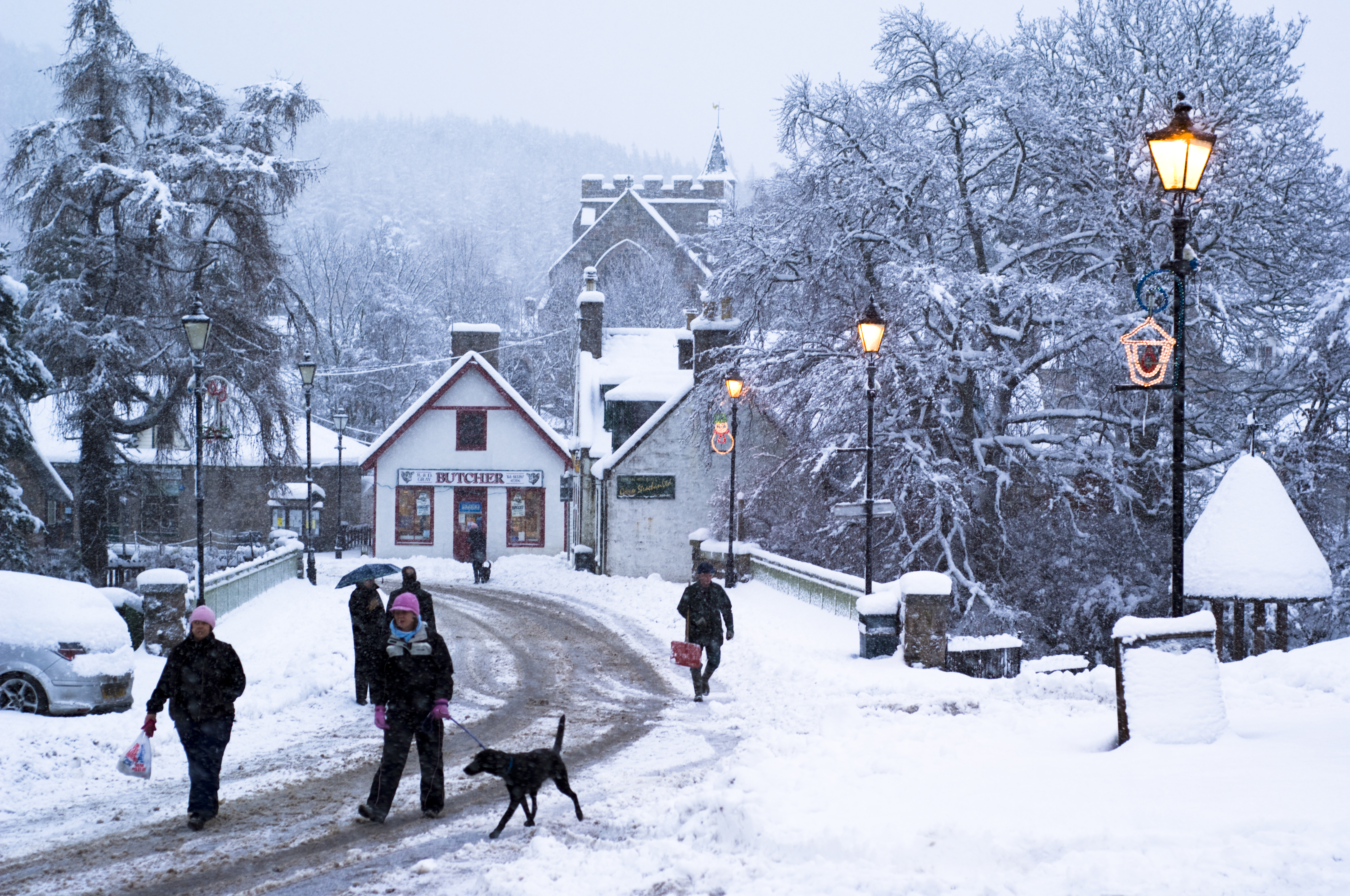 (Picture: Photolibrary/Getty) Snowfall in Braemar village in the Scottish highlands (Cairngorms National Park), dog and villagers in the main street