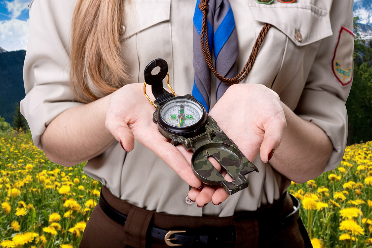 Girl scout holding the compass traveling in the mountains; Shutterstock ID 241929178