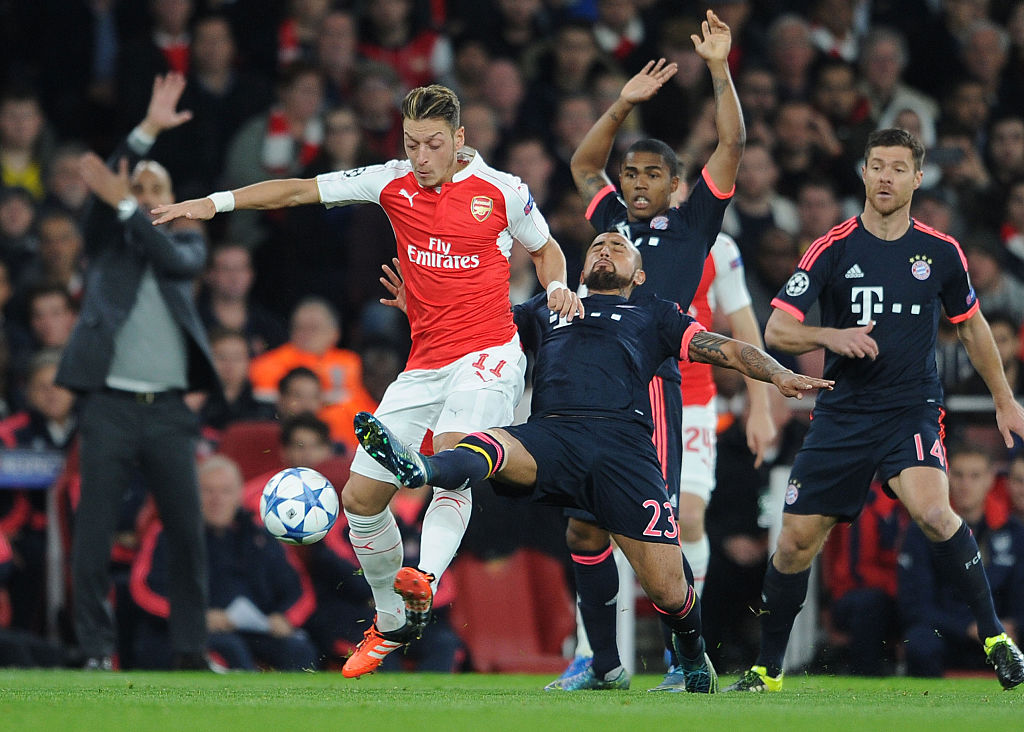 LONDON, ENGLAND - OCTOBER 20: Mesut Ozil of Arsenal is challenged by Arturo Vidal of Bayern during the UEFA Champions League match between Arsenal and Bayern Munich on October 20, 2015 in London, United Kingdom. (Photo by David Price/Arsenal FC via Getty Images)