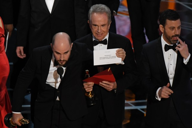 "US actor Warren Beatty (C) shows the card reading Best Film 'Moonlight"" after mistakingly reading ""La La Land"" initially at the 89th Oscars on February 26, 2017 in Hollywood, California. / AFP PHOTO / Mark RALSTONMARK RALSTON/AFP/Getty Images"